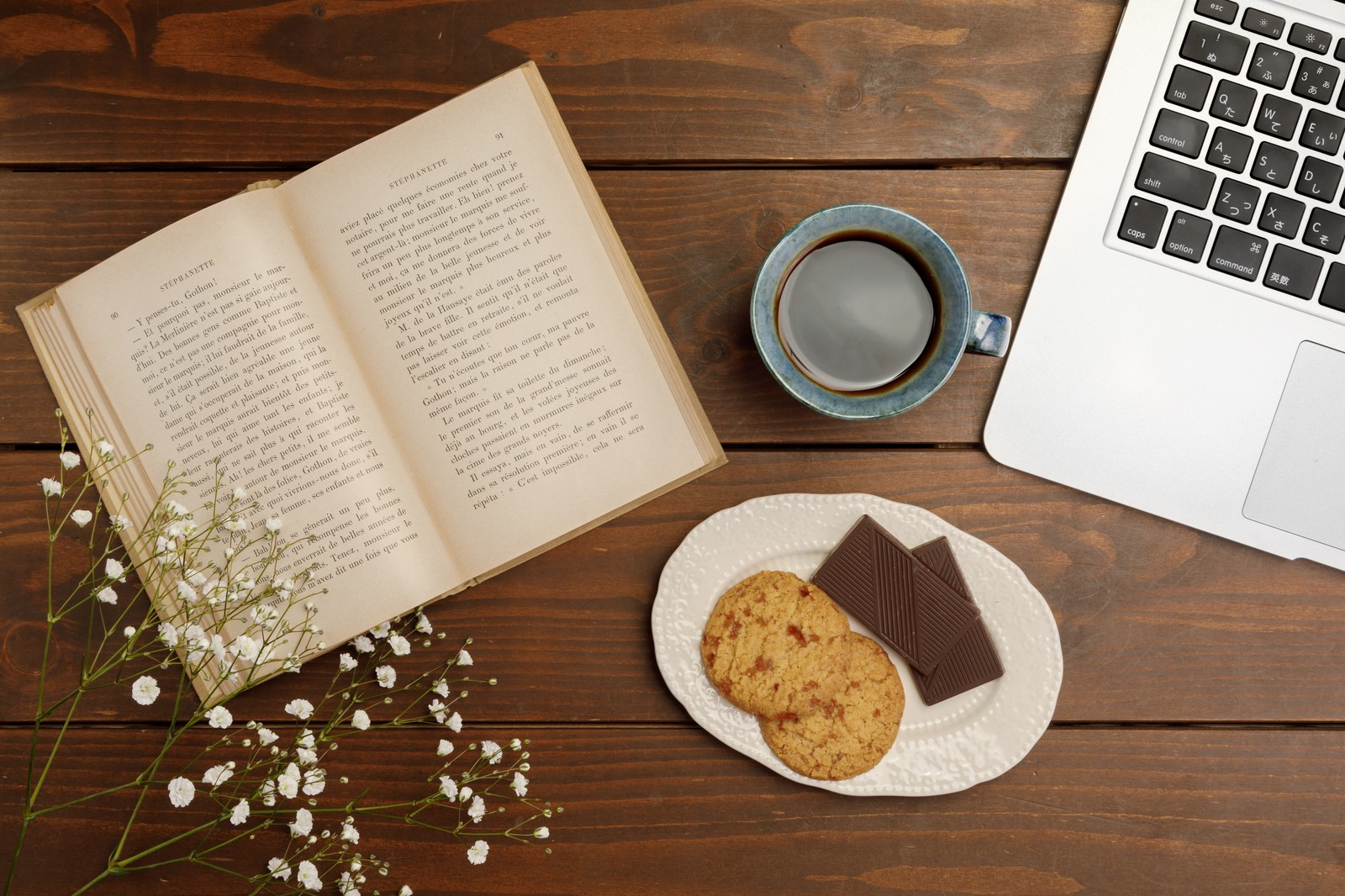 テーブルの上に置かれた英語の書籍とクッキーとコーヒー