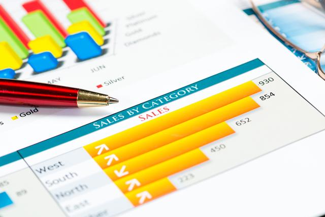 売上を表す黄色い棒グラフと赤いボールペン