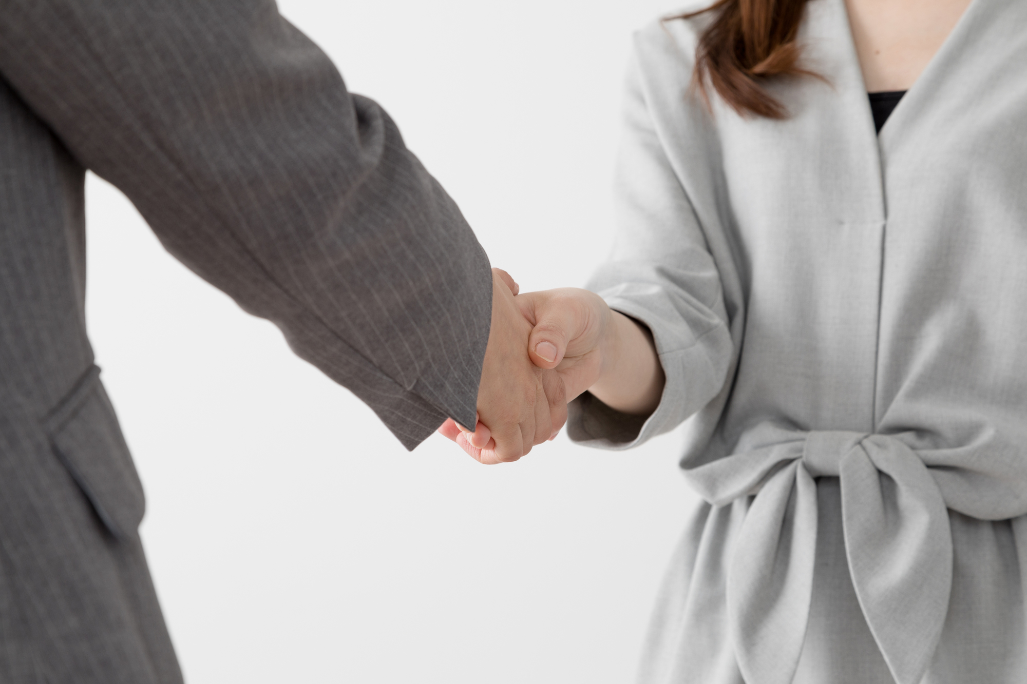 クライアントの男性と握手する女性の専門家